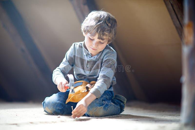 Kleinkindjunge, der bei den Spielzeugwerkzeugen auf Baustelle hilft Lustiges Kind von 6 Jahren Spaß auf dem Errichten der neuen F stockfotos