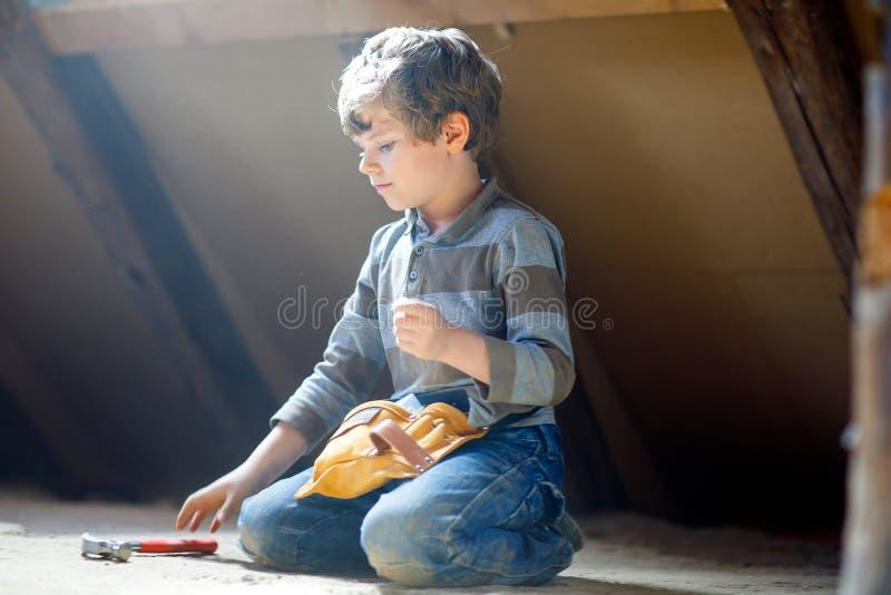 Kleinkindjunge, der bei den Spielzeugwerkzeugen auf Baustelle hilft Lustiges Kind von 6 Jahren Spaß auf dem Errichten der neuen F lizenzfreie stockfotografie