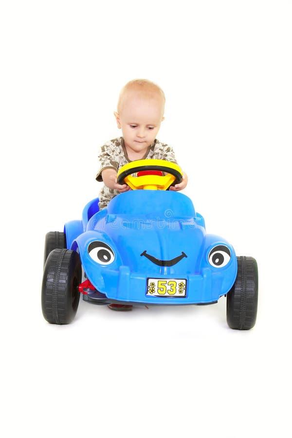 Kleinkindjunge, der ein Spielzeugauto antreibt stockfotos