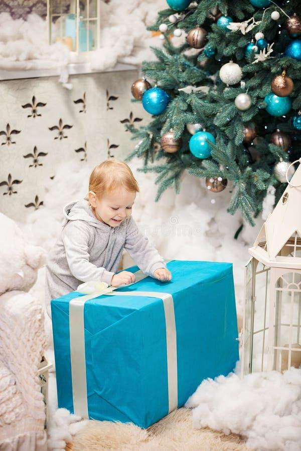 Kleinkindjunge, der einen Kasten mit Weihnachtsgeschenk öffnet stockfoto