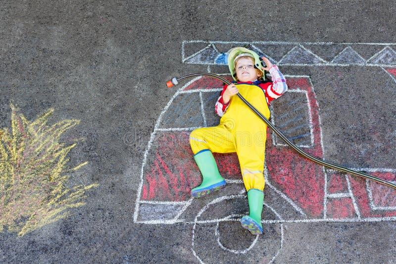 Kleinkindjunge in der Feuerwehrmannuniform, die Spaß mit Löschfahrzeugbildzeichnung mit bunter Kreide auf Asphalt hat lizenzfreie stockbilder