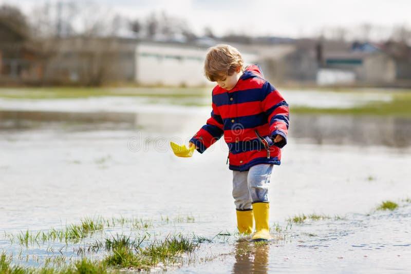Kleinkindjunge, der gelbe Regenstiefel trägt und in Pfütze am warmen sonnigen Frühlingstag geht und springt Glückliches Kind here stockfoto