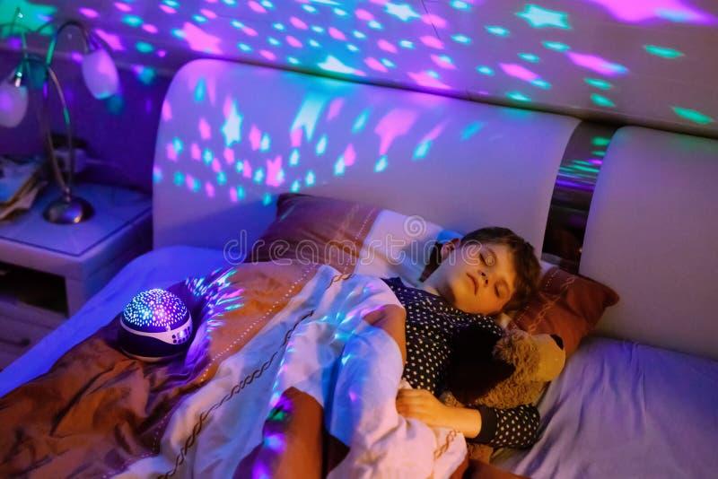 Kleinkindjunge, der im Bett mit bunter Lampe schläft Schulkind, das Pl?schspielzeug tr?umt und h?lt Kind ver?rgert von der Dunkel lizenzfreies stockfoto