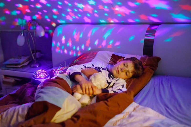 Kleinkindjunge, der im Bett mit bunter Lampe schläft Schulkind, das Pl?schspielzeug tr?umt und h?lt Kind ver?rgert von der Dunkel stockfoto