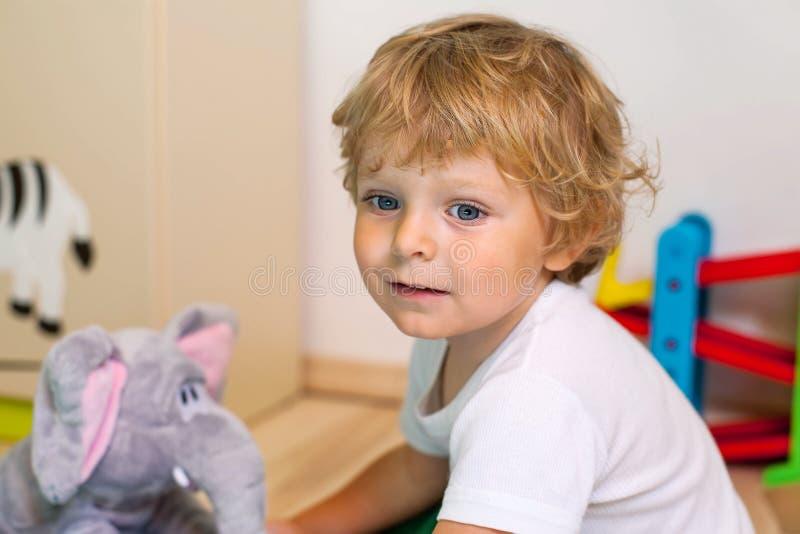 Kleinkindjunge, der mit vielen bunten Spielwaren Innen spielt stockfotografie