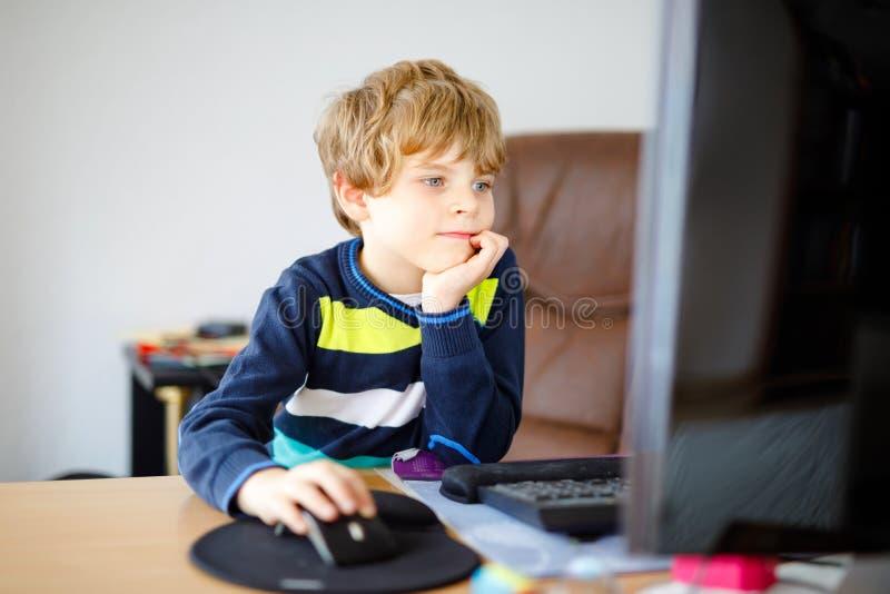 Kleinkindjunge, der Schulhausarbeit auf Computernotizbuch macht Glückliches gesundes Kind, das Informationen über Internet sucht  stockbilder