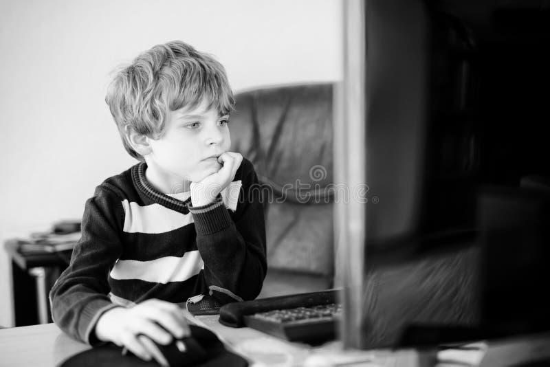 Kleinkindjunge, der Schulhausarbeit auf Computernotizbuch macht Glückliches gesundes Kind, das Informationen über Internet sucht  lizenzfreies stockbild