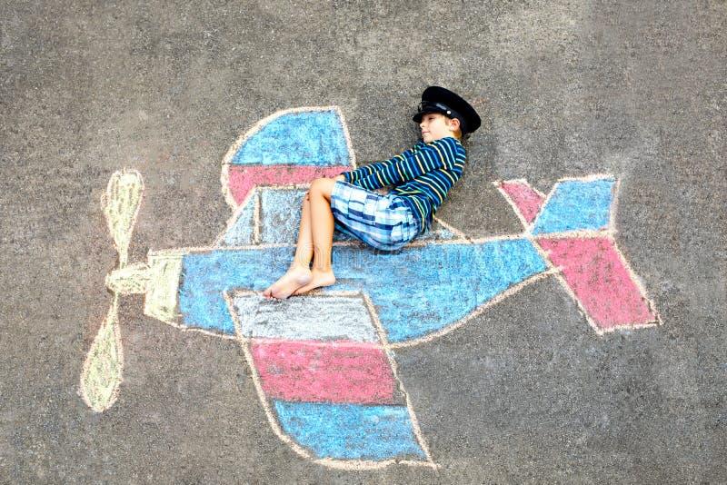 Kleinkindjunge, der Spaß mit mit Flugzeugbildzeichnung mit bunten Kreiden auf Asphalt hat Kindermalerei mit Kreide stockbilder