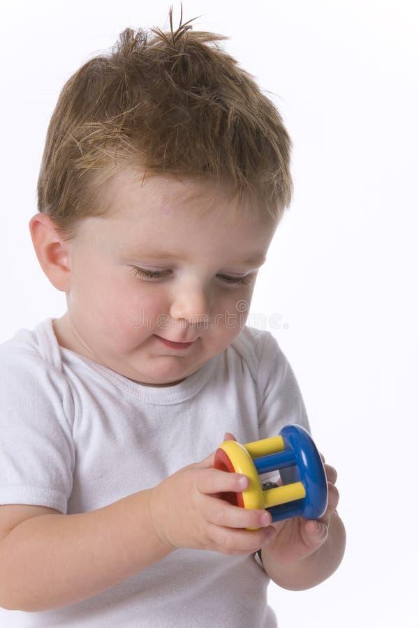 Kleinkindjunge, der Spielzeug betrachtet lizenzfreie stockbilder