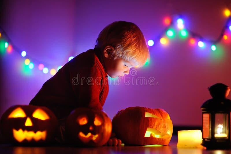 Kleinkindjunge, der zuhause mit Halloween-Kürbisen spielt stockfotos
