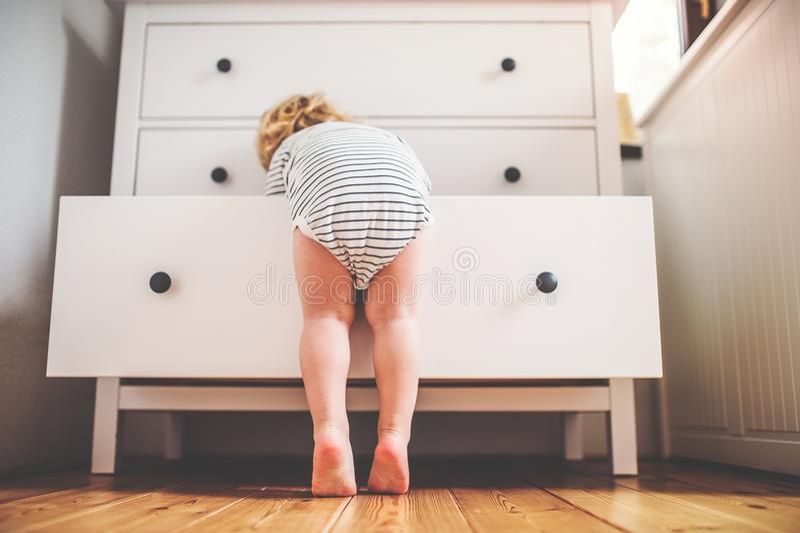 Kleinkindjunge in einer gefährlichen Situation zu Hause stockfotografie