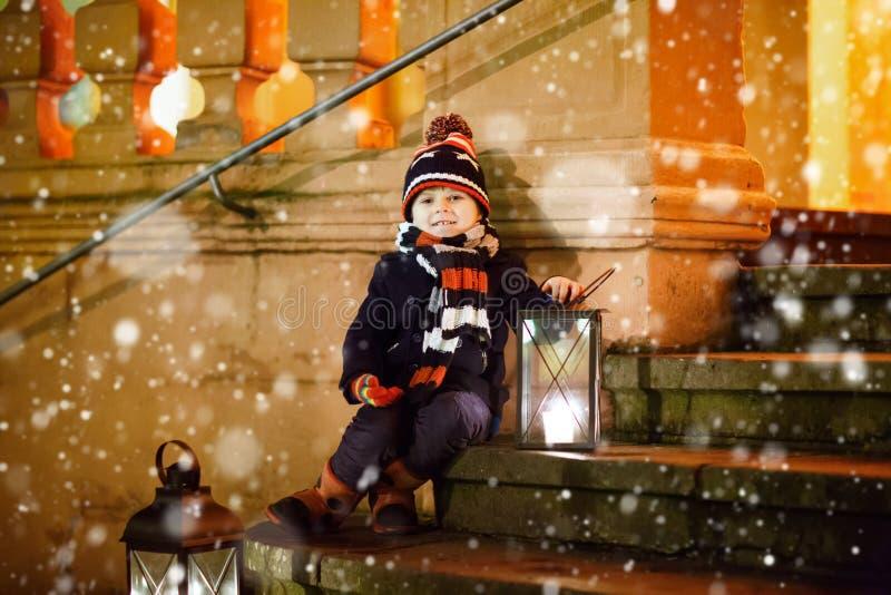 Kleinkindjunge mit Weihnachtslaterne nahe Kirche stockfotografie
