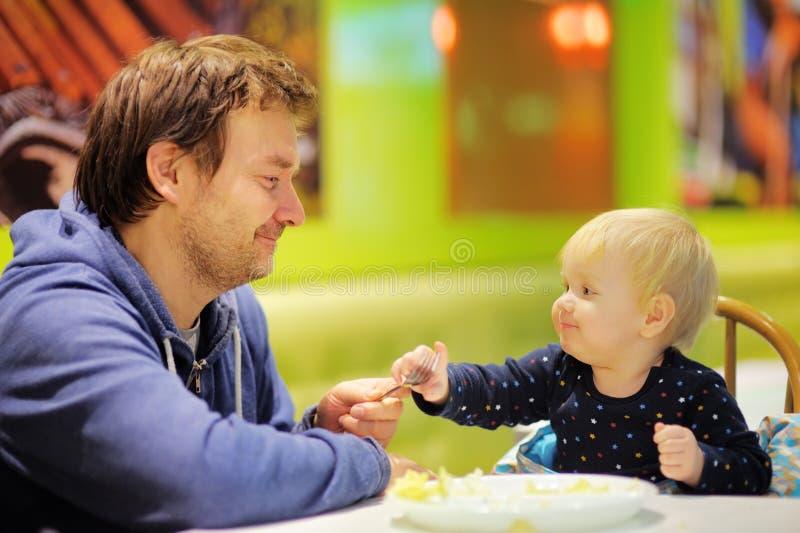 Kleinkindjunge und sein Vater am Café stockbild