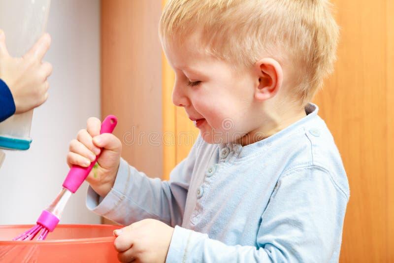 Kleinkindjungenkochen, Kuchen in der Schüssel machend stockfotografie