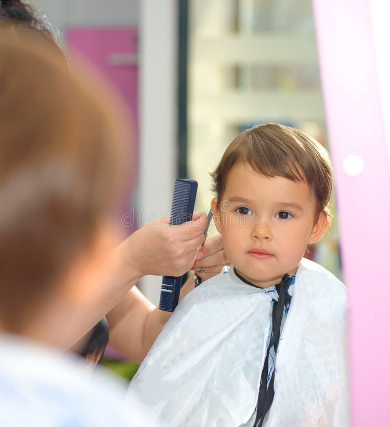 Kleinkindkind, das seinen ersten Haarschnitt am Salon erhält stockbild