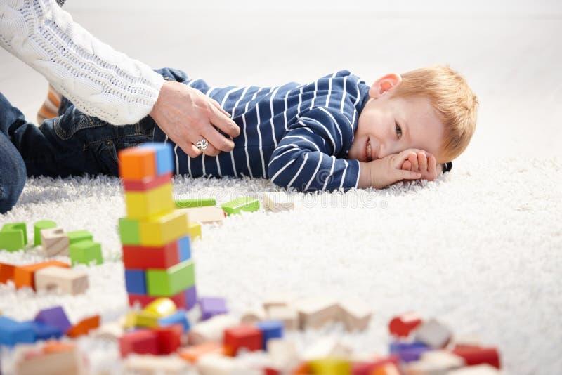 Kleinkindlächeln gekitzelt von der Mutter lizenzfreie stockbilder