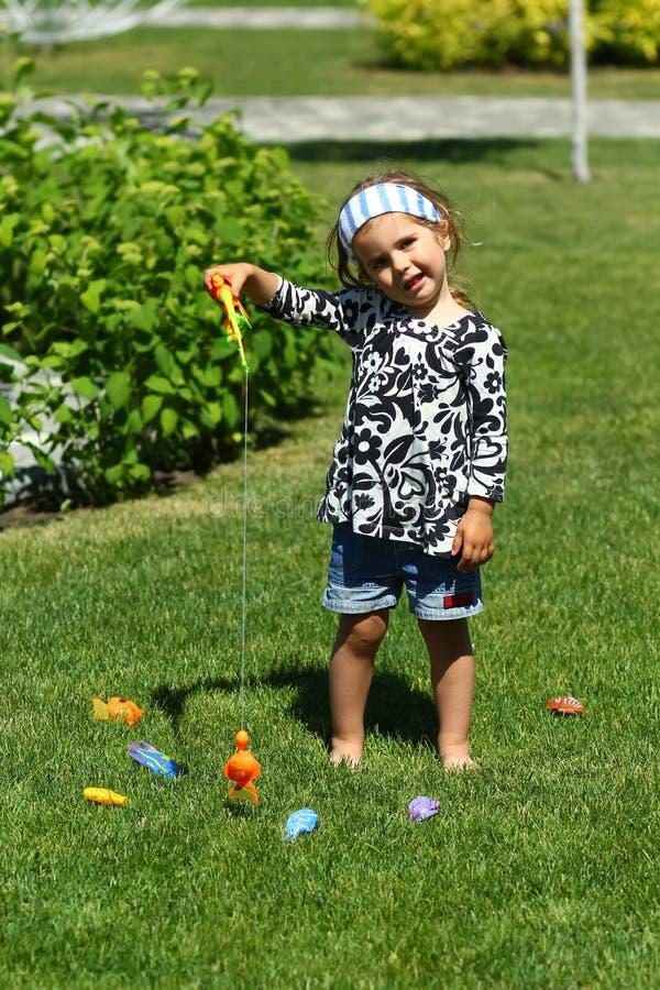 Kleinkindmädchen 'Fischen 'auf dem sonnenbeschienen Sommerrasen lizenzfreie stockfotografie