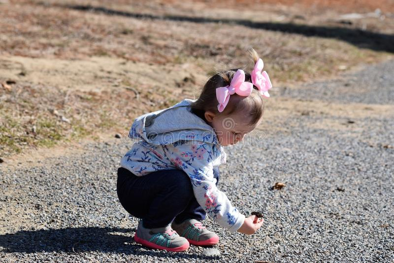 Kleinkindmädchen, das Felsen aufhebt lizenzfreie stockbilder