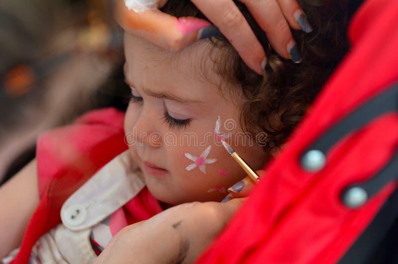 Kleinkindmädchen, das ihr Gesicht gemalt vom Gesichtsmalereikünstler erhält stockbild