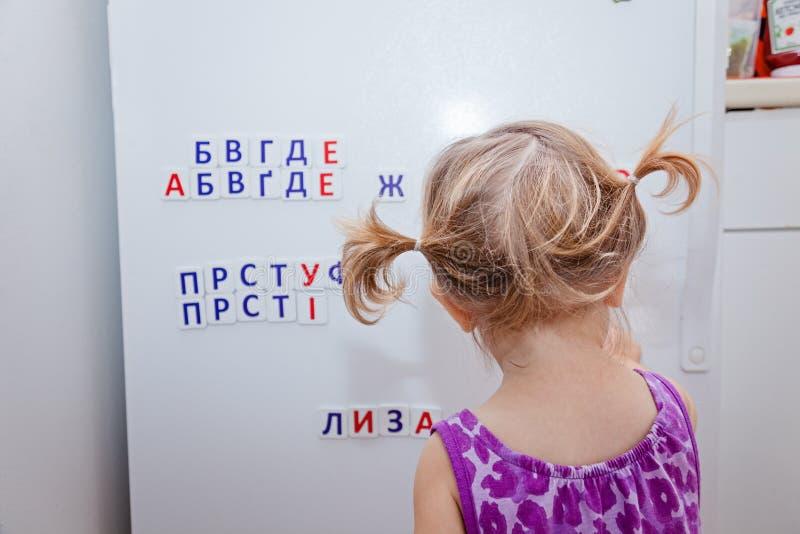 Kleinkindmädchen, das mit russischen Buchstaben des Magneten auf Kühlschrank spielt Lernen, Wörter zu machen Früher Messwert stockbild