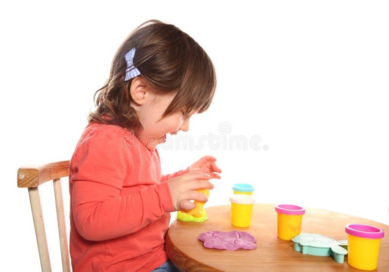 Kleinkindmädchen, das mit Spiel Doh spielt lizenzfreies stockfoto