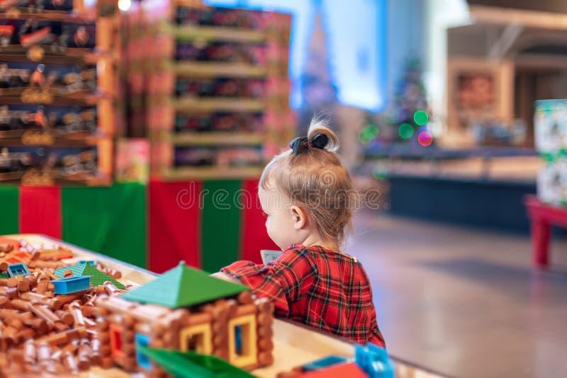 Kleinkindmädchen, das mit Spielwaren bei der Aufwartung, um Sankt zu besuchen spielt lizenzfreies stockbild