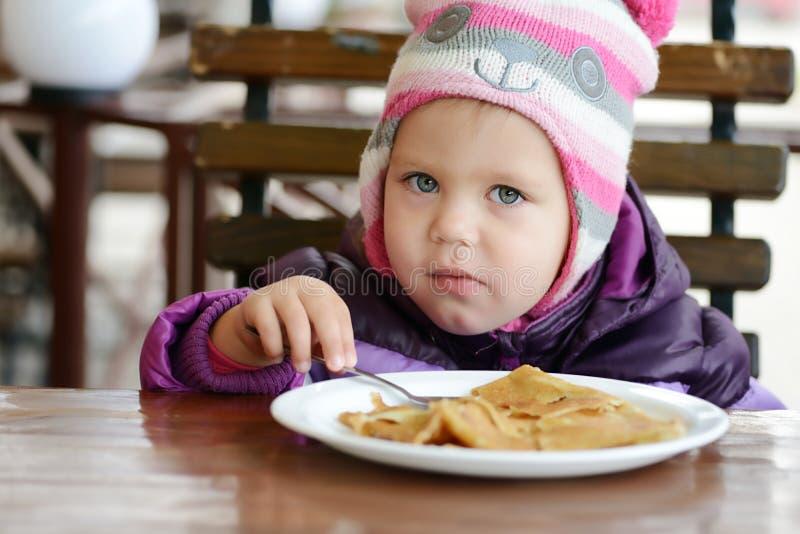 Kleinkindmädchen, das Pfannkuchen isst lizenzfreies stockfoto