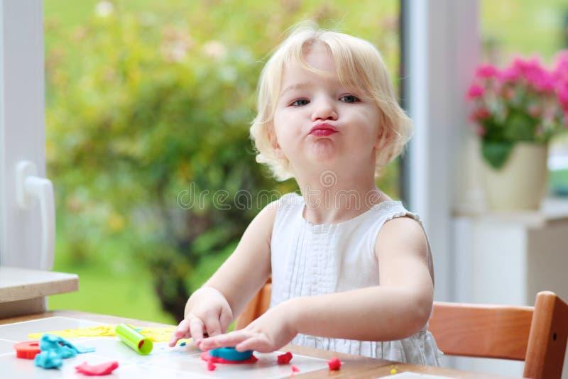 Kleinkindmädchen, das Plätzchen vom Plasticine macht lizenzfreie stockfotos
