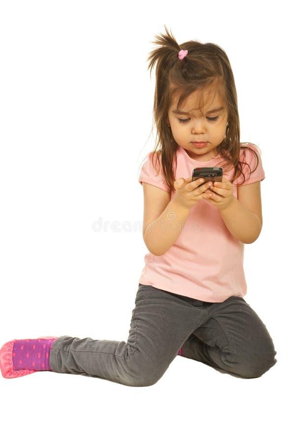 Kleinkindmädchen, das sms Text sendet stockbild