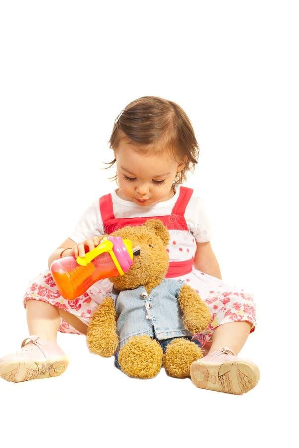 Kleinkindmädchen givng Saft zu ihrem Bärnspielzeug lizenzfreie stockfotos
