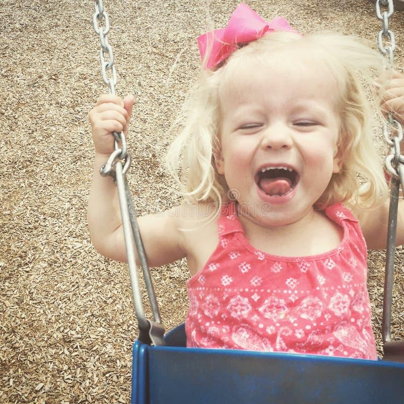 Kleinkindmädchen glücklich auf dem Schwingen lizenzfreie stockfotografie