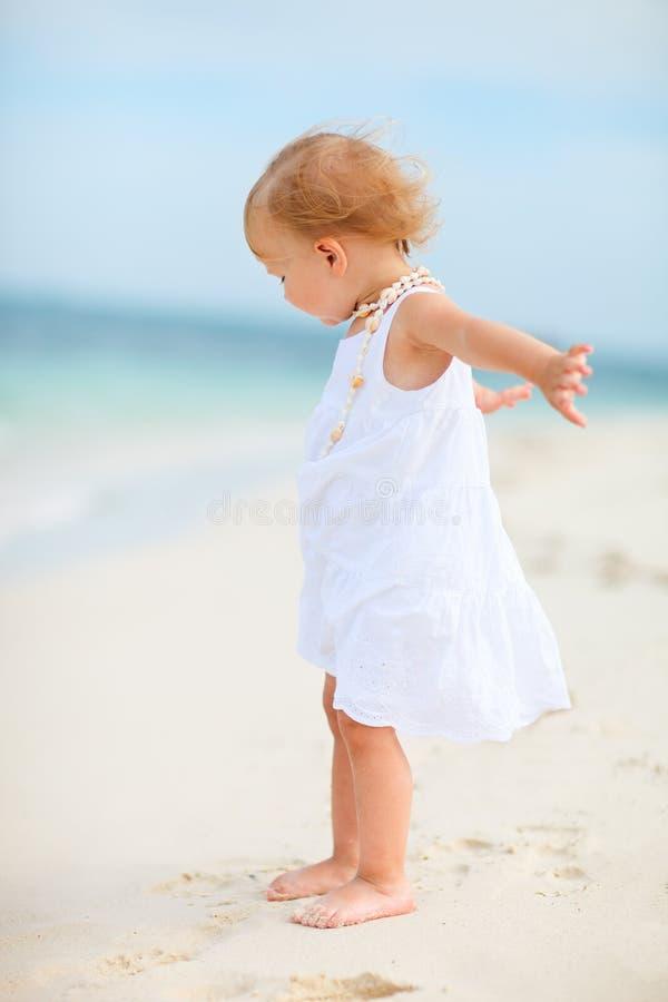 Kleinkindmädchen im weißen Kleid am Strand stockfotografie