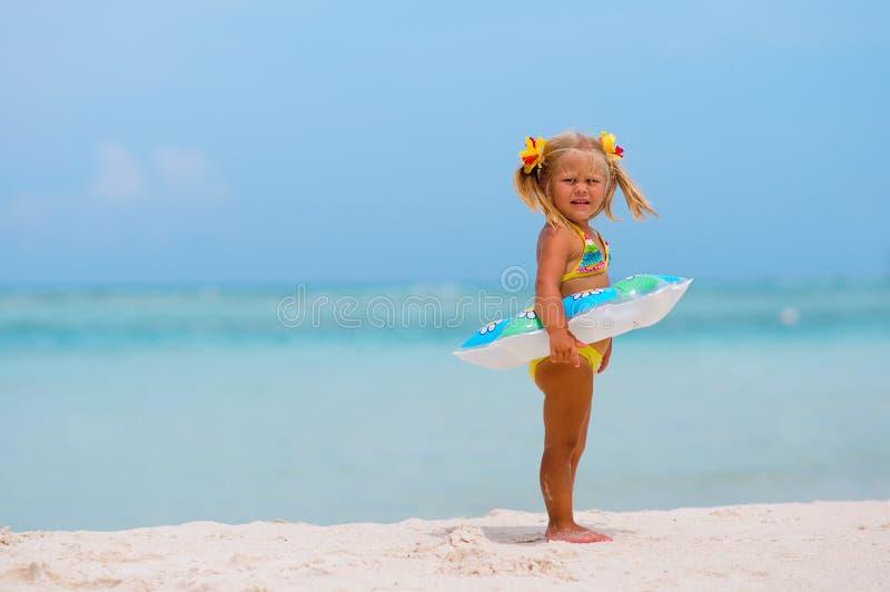 Kleinkindmädchen mit aufblasbarem Kreis auf Strand stockfotos