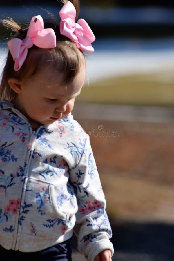 Kleinkindmädchen mit den Rosabögen, die unten schauen stockfotografie