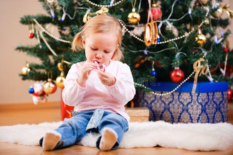 Kleinkindmädchen mit Weihnachtssüßigkeit lizenzfreie stockbilder