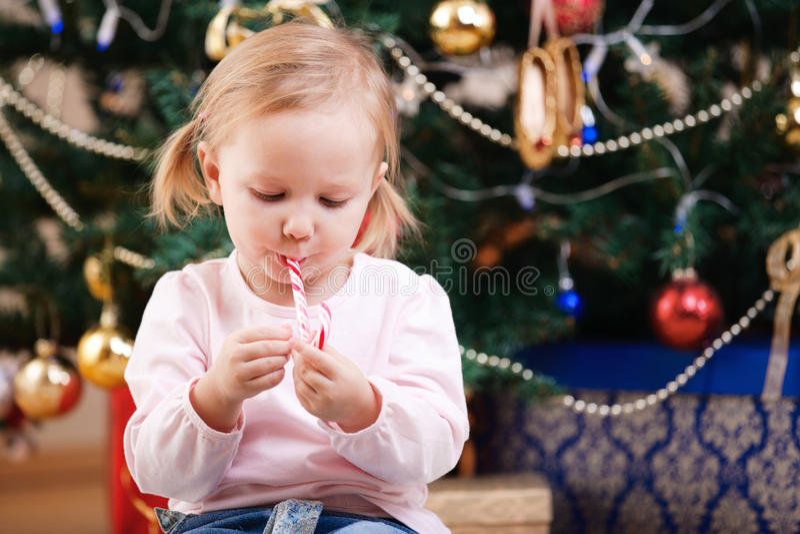 Kleinkindmädchen mit Weihnachtssüßigkeit stockfotos