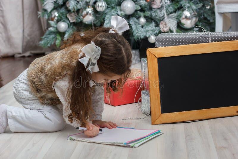 Kleinkindmädchen-Schreibensbuchstabe mit Wünschen zu Santa Claus am Weihnachtstag stockbilder