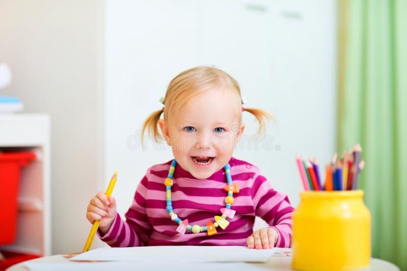 Kleinkindmädchenzeichnung mit Bleistiften stockbild
