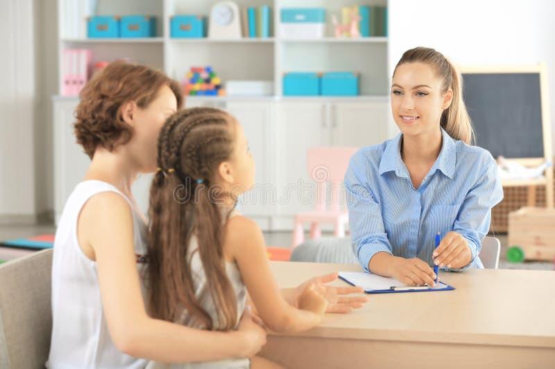 Kleinkindpsychologe, der mit Familie im Büro arbeitet lizenzfreie stockbilder
