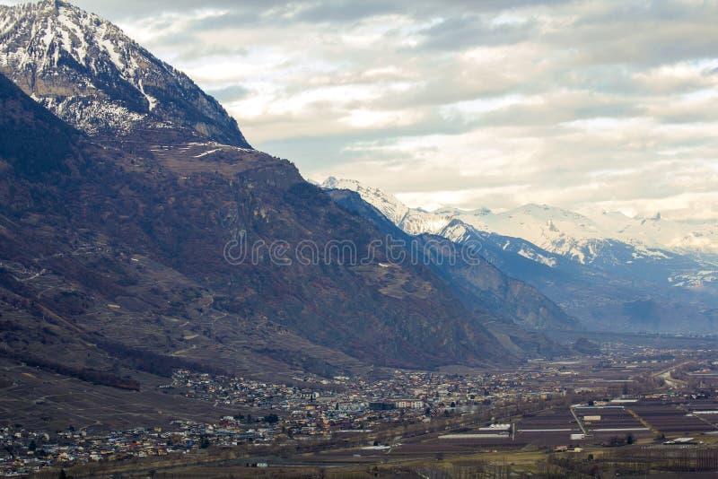 Kleinstadt im Tal am Fuß des ausgezeichneten Alpenberges, die Schweiz Ruhiges Leben auf Hintergrund von fantastischen Spitzen bed stockbilder