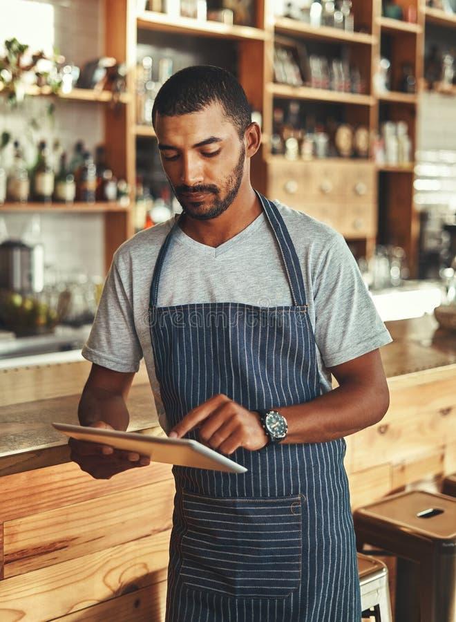 Kleinunternehmer an seiner Kaffeestube unter Verwendung der digitalen Tablette stockfotos