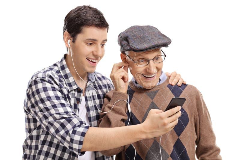 Kleinzoon die aan muziek op een telefoon met zijn grootvader luisteren royalty-vrije stock afbeeldingen