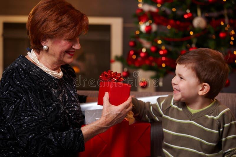 Kleinzoon die aanwezige Kerstmis geven stock fotografie