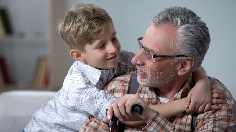 Kleinzoon die grootvader met liefde, kostbare familienotulen, bejaarde zorg omhelzen royalty-vrije stock foto