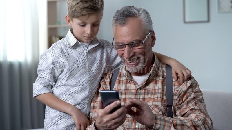Kleinzoon die grootvader verklaren hoe te om smartphone, gemakkelijke app voor bejaarden te gebruiken stock fotografie