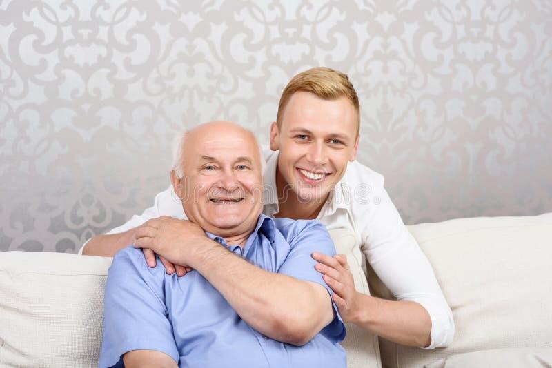 Kleinzoon die lichtjes zijn grootvader omhelzen royalty-vrije stock foto's