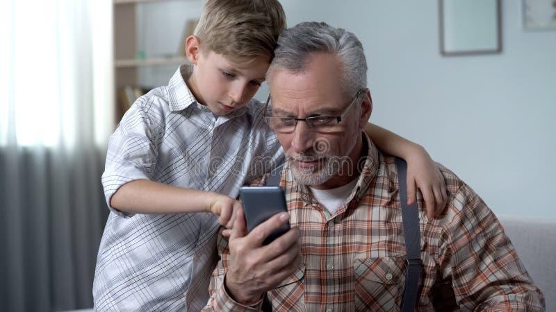Kleinzoon die opa verklaren hoe te om smartphone, gemakkelijke toepassing voor bejaarden te gebruiken stock foto's