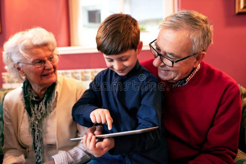 Kleinzoon die zijn grootouders onderwijzen hoe te om een tablet te gebruiken stock fotografie