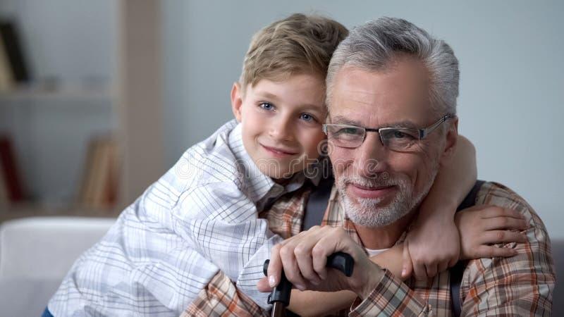 Kleinzoon knuffelende grootvader met liefde, kostbare familienotulen, bejaarde zorg royalty-vrije stock foto's