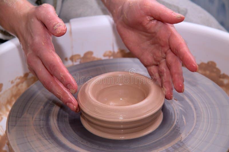 Kleipot op een pottenbakkerswiel en handen stock foto's